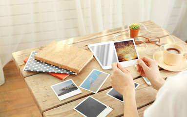 Woman holding photos from vacation at wooden table indoors