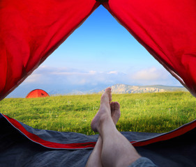 Image human legs lying in tourist tent