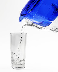 Pouring water into glass on grey background