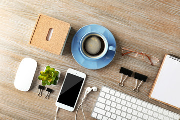 Keyboard, phone, notebook and cup of coffee on a wooden desk background, top view