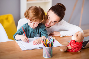 Mother and child drawing while sitting