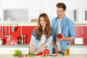 Couple cooking salad in kitchen