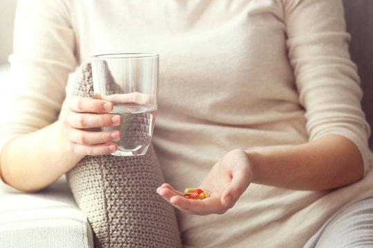 Woman taking vitamins, closeup