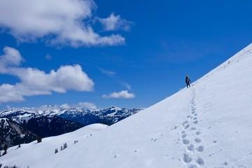 Man climber on steep snow mountain slope. Ruth Mountain near Bellingham, North Cascades National park, Washington, USA.