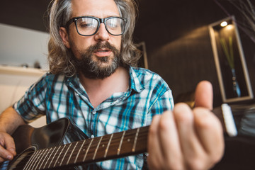 Man sitting in sofa and playing guitar at home
