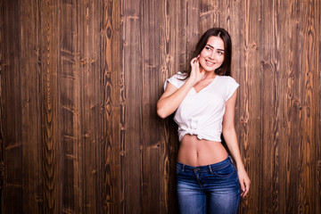 Young girl with nice smile against wooden wall