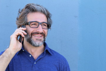 Casual man talking on mobile phone isolated on blue with copy space