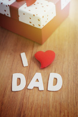 Letter make word I love DAD with heart shape symbol and gift box, celebration Happy Father's day concept. Wood background, vintage style.