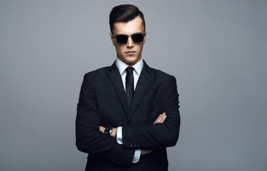 Stylish young man in suit and sunglasses. Business style. Fashionable image. Office worker. Sexy man standing and looking at the camera