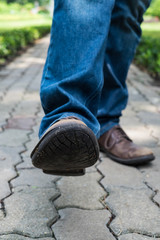 Man wearing jeans walking on the path to the park or garden