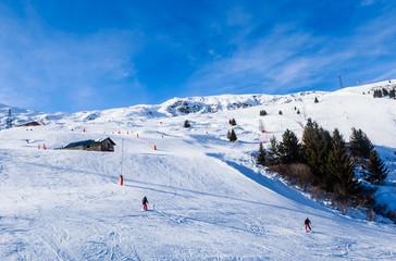 Unidentified skiers enjoy skiing at the slope in the  Alps.  Ski resort Meribel