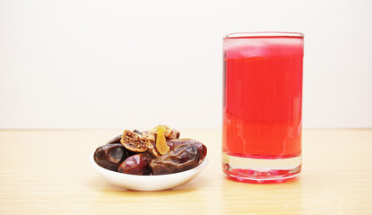 dates and a glass of red syrup drink.