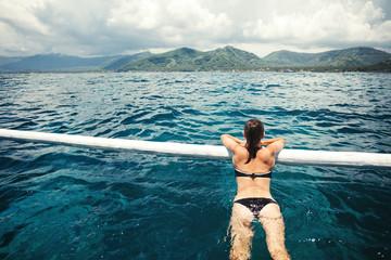 Woman relaxing in deep ocean near the boat