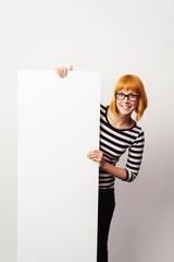 lächelnde frau zeigt ein weißes schild
