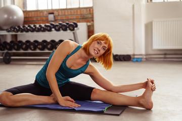 frau dehnt beine und fuß im fitness-center