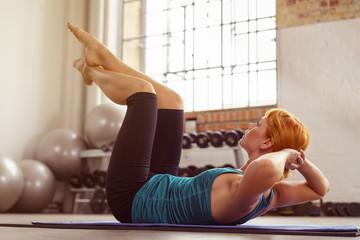 frau macht situps im fitness-studio