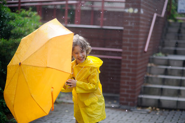 Boy 8-9 years walk with a yellow umbrella in the yard during rain.