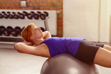frau trainiert ihre bauchmuskulatur mit einem gymnastikball