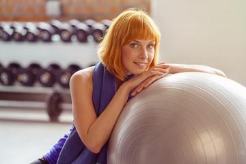 lächelnde, sportliche frau stütz sich auf einen gymnastikball