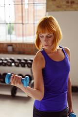 frau trainiert mit hanteln im fitnessstudio