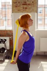 frau trainiert rücken und arme mit einem pilatesband