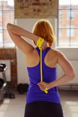 frau trainiert im sport-studio mit einem pilatesband