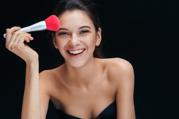 Young beautiful girl with make up pink brush on black background. Youth and skin care concept