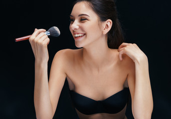 Charming young woman with brush for powder. Photo of smiling girl on black background. Youth and skin care concept