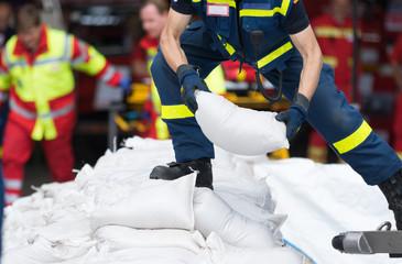 Helfer transportiert Sandsäcke