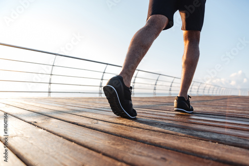 Legs of african young man running on wooden terrace for Terrace jogging track