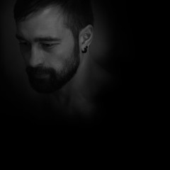 Portrait of a man with a beard and an earring on a black background