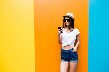 Pretty woman in sunglasses and hat text massege on phone over  color wall background