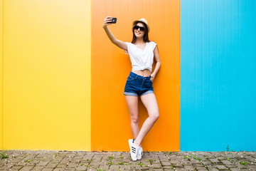 Fashion happy woman makes self portrait on smartphone  over city color wall background