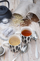 two cups 1 black tea rooibos and other fennel with teapot in the