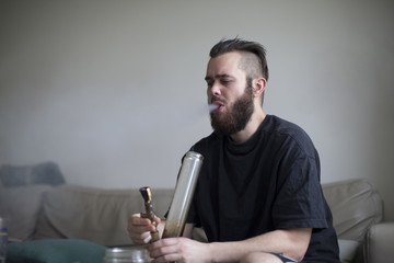 Young Man Smoking Drugs In Bong At Home