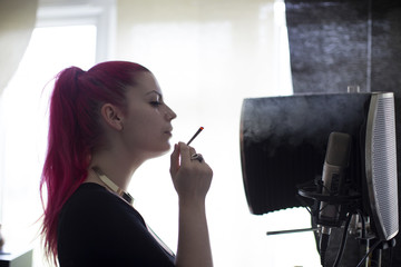 Young Woman Smoking Joint At Home And Recording Music