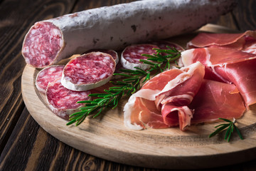 Spanish tapas with jamon and sausage on a wooden background