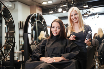 Beautiful blonde female hairdresser holding scissors and comb