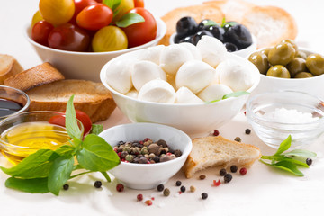 fresh ingredients for salad with mozzarella on white table