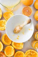 White bowl with wooden squeezer, squeezed oranges and fresh orange juice in jars. Selective focus on squeezer.