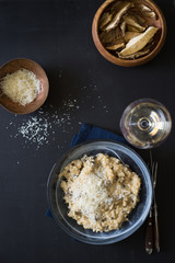 Dried porcini mushrooms risotto sprinkled with grated parmesan cheese. Selective focus.