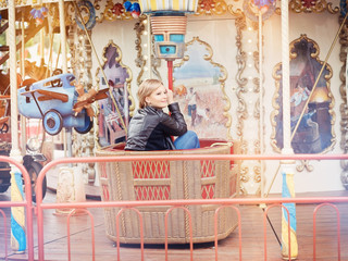 Young beautiful blond woman sitting on a Merry-Go-Round (carouse
