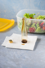 Empty small bottle with olive oil and balsamic vinegar used to  season takeaway salad. Selective focus.