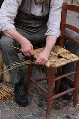 man mender of chairs while repairing old wooden chair