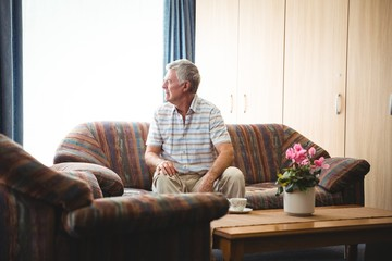 Senior man sitting on a couch Wall mural