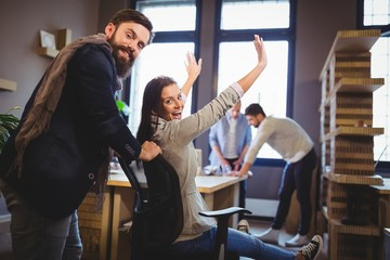 Happy coworkers enjoying by desk in creative office