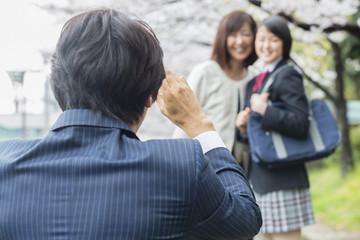 桜の下で写真を撮る家族
