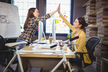 Female colleagues high fiving at computer desk