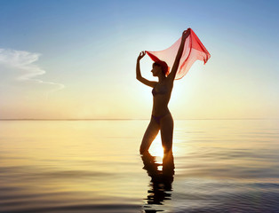 Young woman with red cloth against background of sea sunset