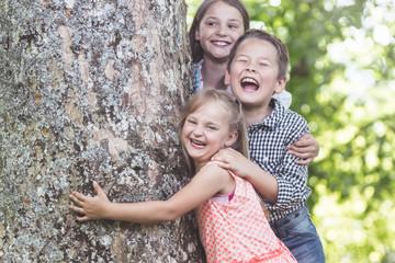 Three Children laughing under big old Tree
